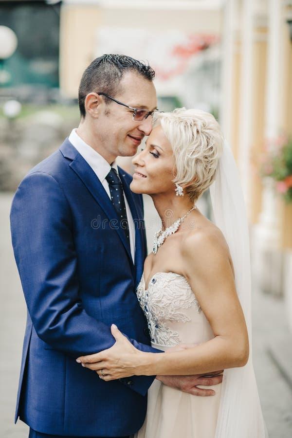 Recém-casados de sorriso felizes que andam fora, beijando e abraçando imagens de stock