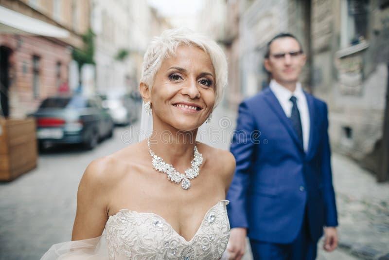 Recém-casados de sorriso felizes que andam fora, beijando e abraçando imagem de stock