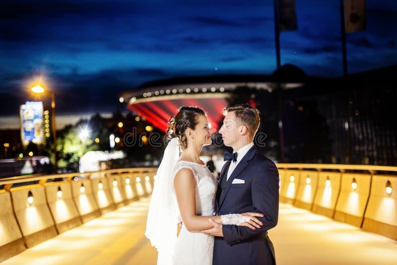 Recém-casados lindos na ponte da cidade na noite imagem de stock