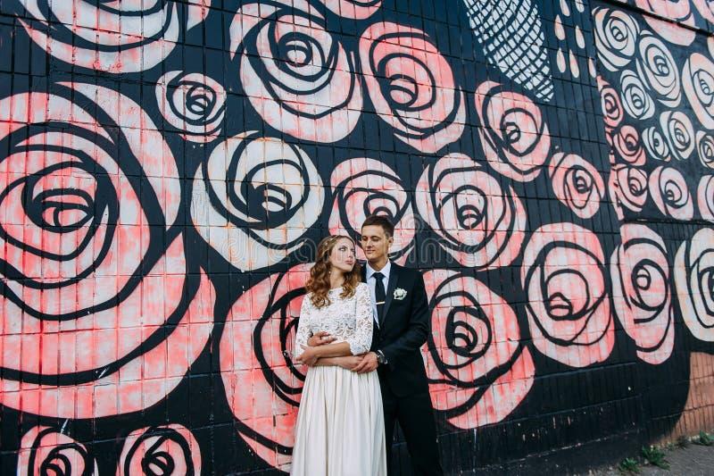 Recém-casados que abraçam ao lado da parede dos grafittis Pares novos do casamento fotografia de stock