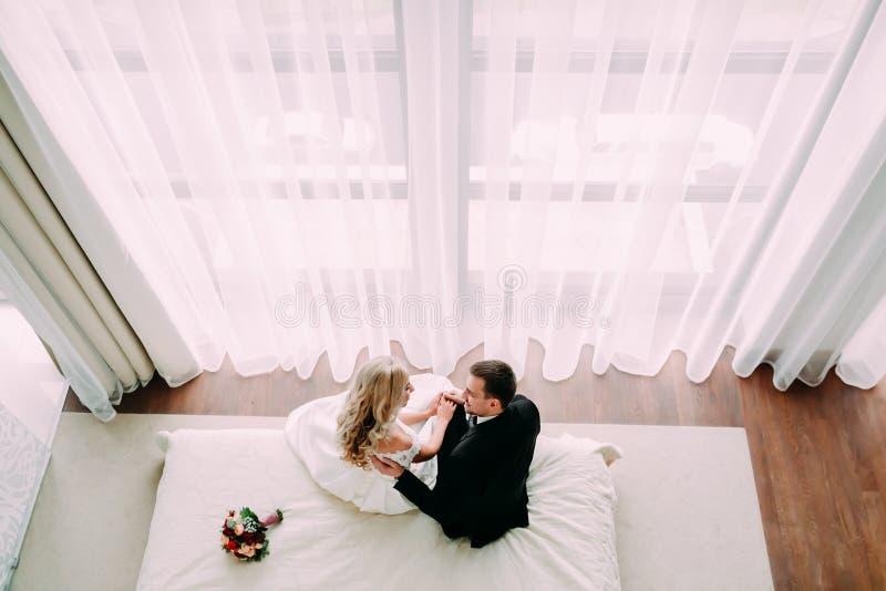 Recém-casados que abraçam na cama na sala de hotel clara luxuosa foto de stock royalty free