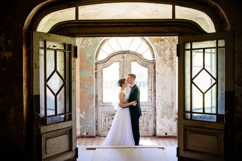 Recém-casados que abraçam na porta em uma casa velha imagens de stock royalty free