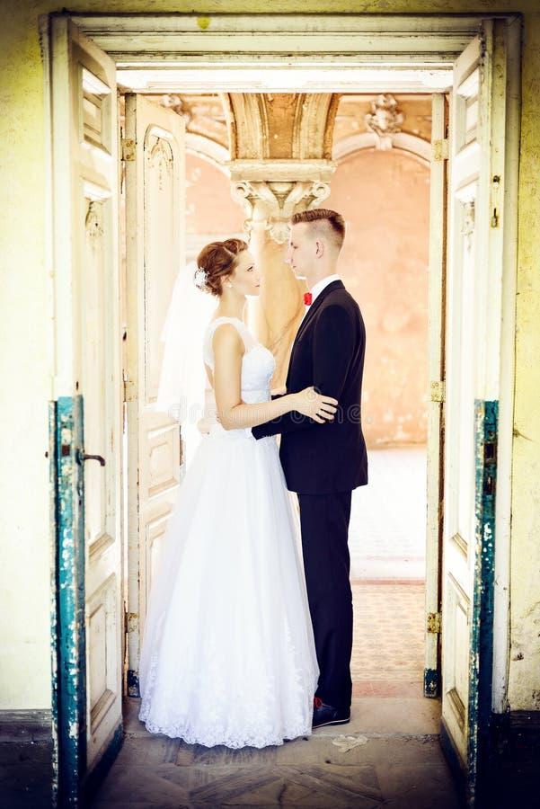 Recém-casados que abraçam na porta em uma casa velha fotografia de stock royalty free