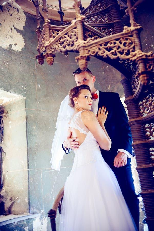 Recém-casados que abraçam perto das escadas velhas Dia do casamento imagem de stock