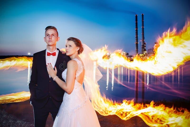 Recém-casados que abraçam perto do lago na noite fotografia de stock royalty free