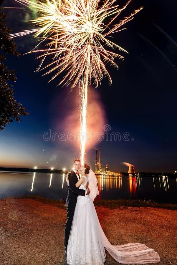 Recém-casados que beijam perto do lago na noite - fogos-de-artifício fotografia de stock