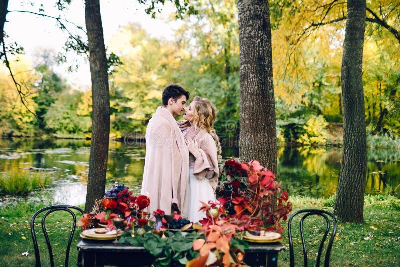 Recém-casados que beijam sob a manta ao lado da tabela festiva Noiva e noivo no parque Casamento do outono artwork fotografia de stock royalty free