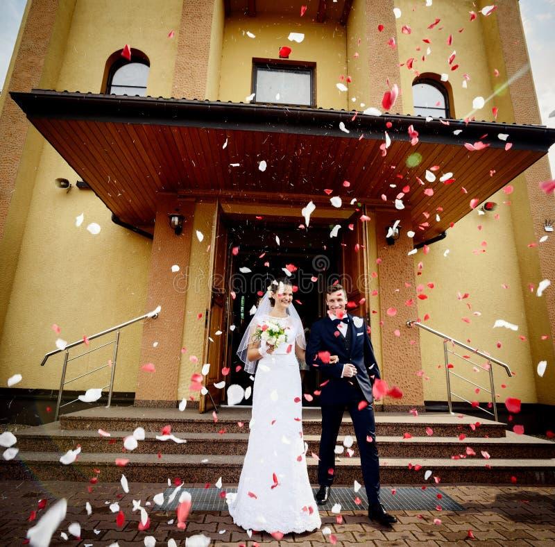 Recém-casados que saem da igreja após a cerimônia de casamento imagens de stock royalty free