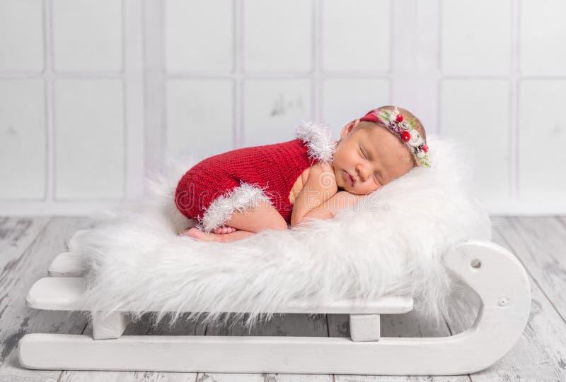 Recém-nascido bonito no romper vermelho no berço do trenó imagens de stock royalty free