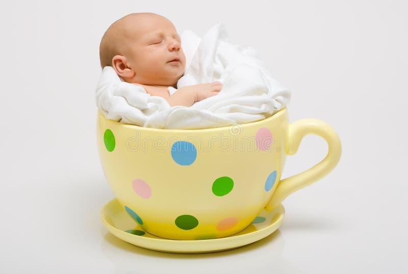 Recém-nascido em um copo manchado amarelo fotografia de stock royalty free