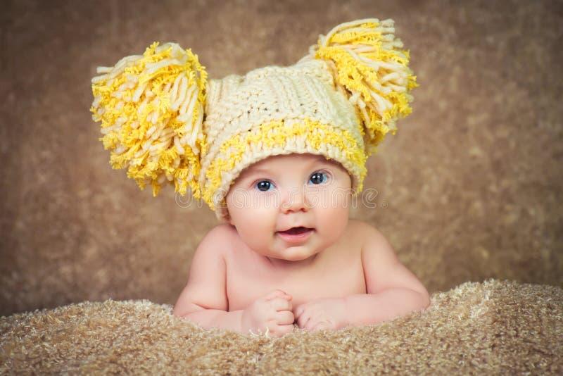 Recém-nascido no chapéu feito malha do inverno em um fundo bege foto de stock