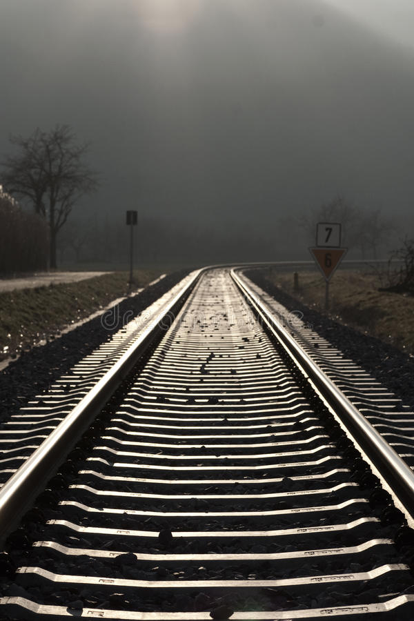 Receding railway track. Scenic view of back lit railway track receding into distance under dark clouds stock images