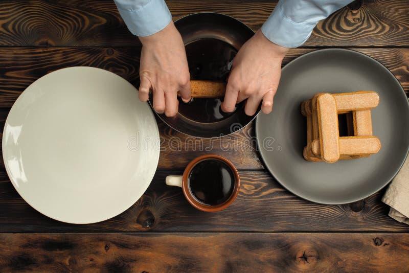Receita do cozimento de uma sobremesa do tiramisu, parte sexta: 'Impregnação do biscoito no café ' fotografia de stock