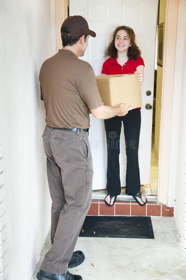 Receiving a Delivery. Girl receiving a package from a delivery man royalty free stock image