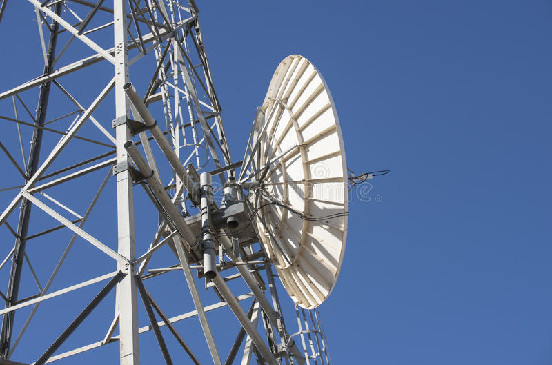Receiving Dish on Telecommunication Tower. A large white metal dish attached to the side of a telecommunication tower stock photo