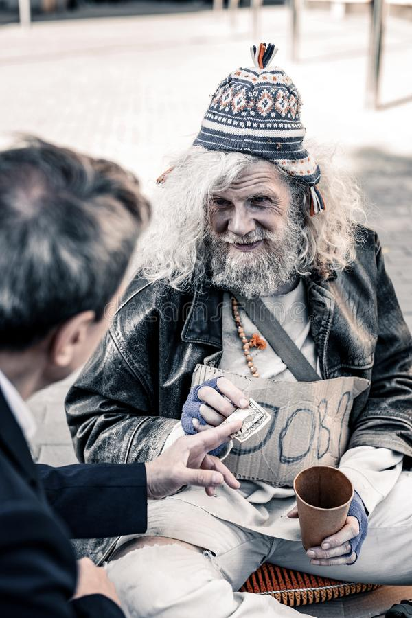 Rich man participating in act of charity while handing money to homeless. Receiving money. Rich men participating in act of charity while handing money to stock image