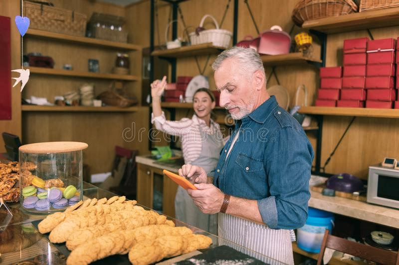 Couple of businessmen receiving orders in their French bakery stock photos