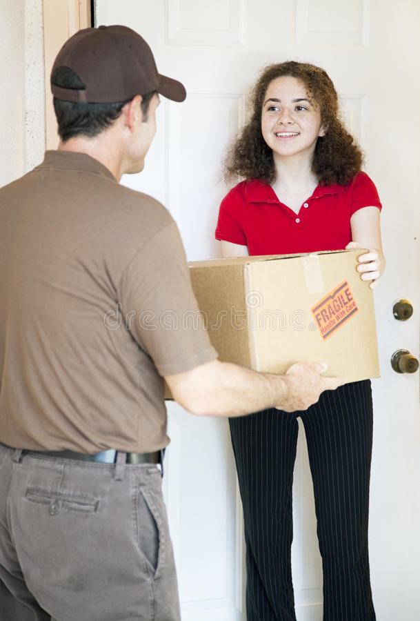 Receiving Package. Young woman at home receives a package from a delivery man royalty free stock image
