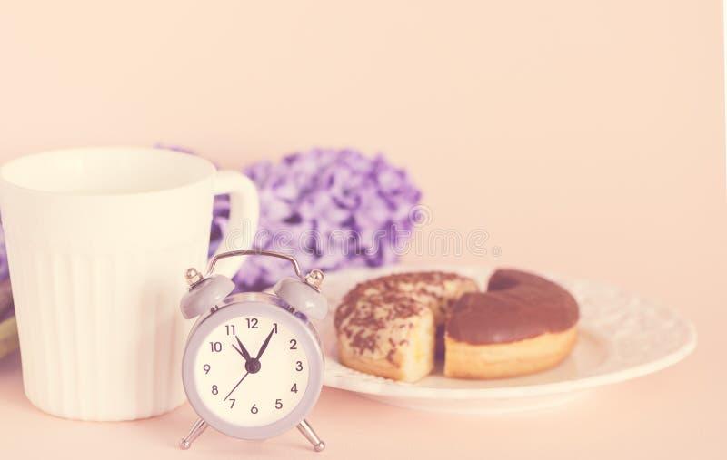 Recent de lenteontbijt met koffie, heerlijke chocolademuffins, bloemen - purpere hyacinten en retro wekker stock foto's