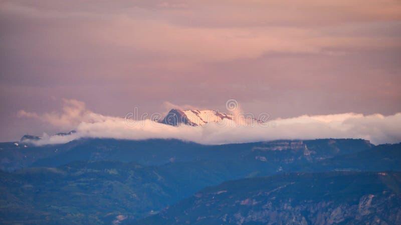 Recente Middag het Lichte Glanzen op Sneeuw Afgedekte Berg boven Dunne Witte Wolkenbank, Griekenland royalty-vrije stock fotografie