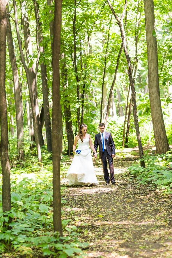Recentemente caminhada do casal nos trajetos do parque que guardam as mãos imagens de stock