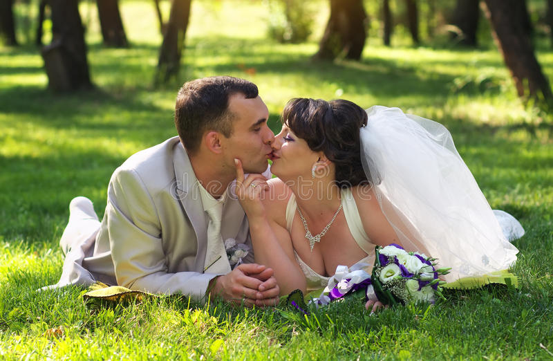Recentemente casal bonito que encontra-se na grama no parque fotografia de stock