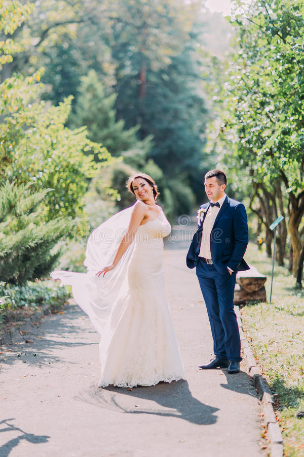 Recentemente casal que levanta no parque ensolarado Noiva brincalhão que mostra seu véu nupcial imagens de stock royalty free