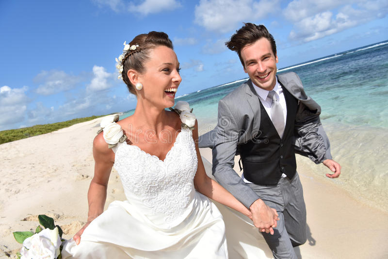Recently married young couple running on the beach royalty free stock photos