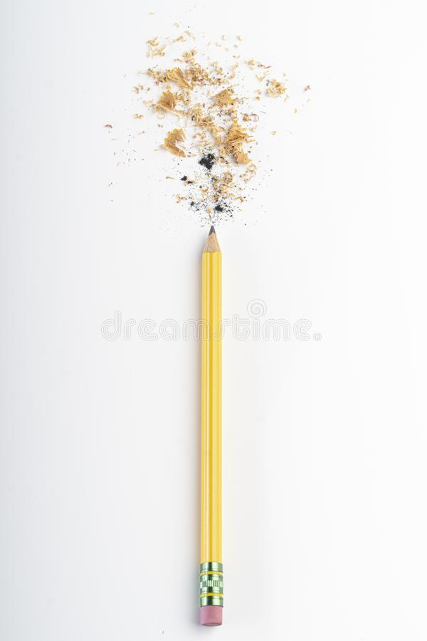 Recently sharpened pencil with wood shavings and mine on a white table stock photos