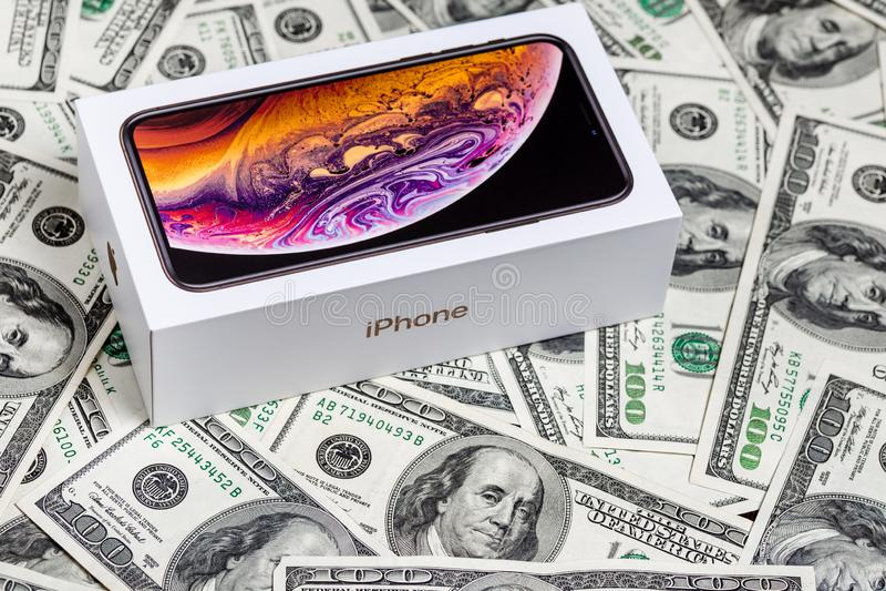 Recentste Iphone XS in ongeopende doos op de achtergrond van Amerikaanse dollarbankbiljetten stock foto's