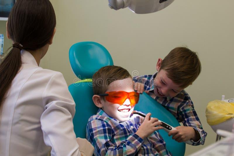 Recepção na odontologia Um rapaz pequeno coloca no sofá com vidros sobre, seu irmão que guarda a lâmpada fotografia de stock royalty free
