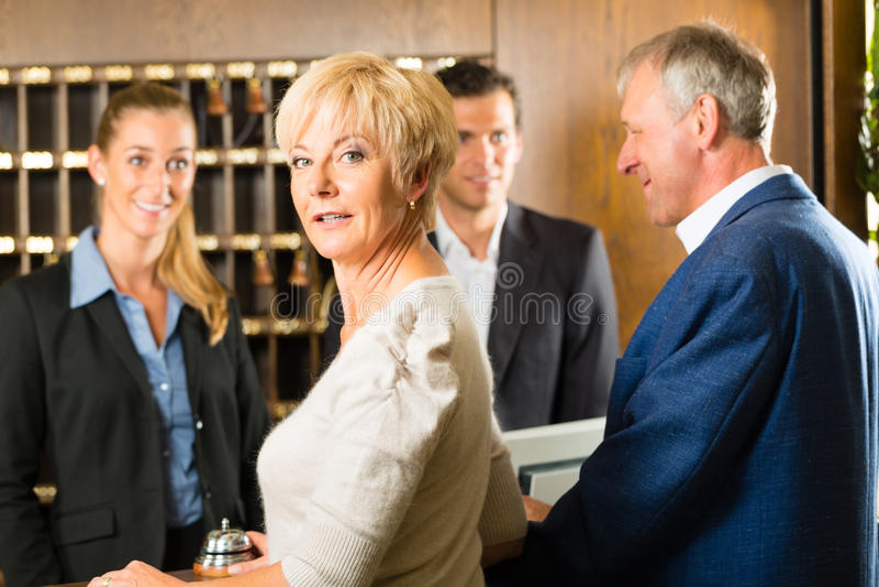 Recepção - os convidados verificam dentro um hotel fotos de stock royalty free
