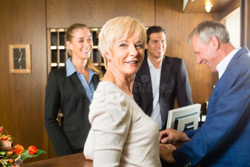 Recepção - os convidados verificam dentro um hotel imagens de stock royalty free