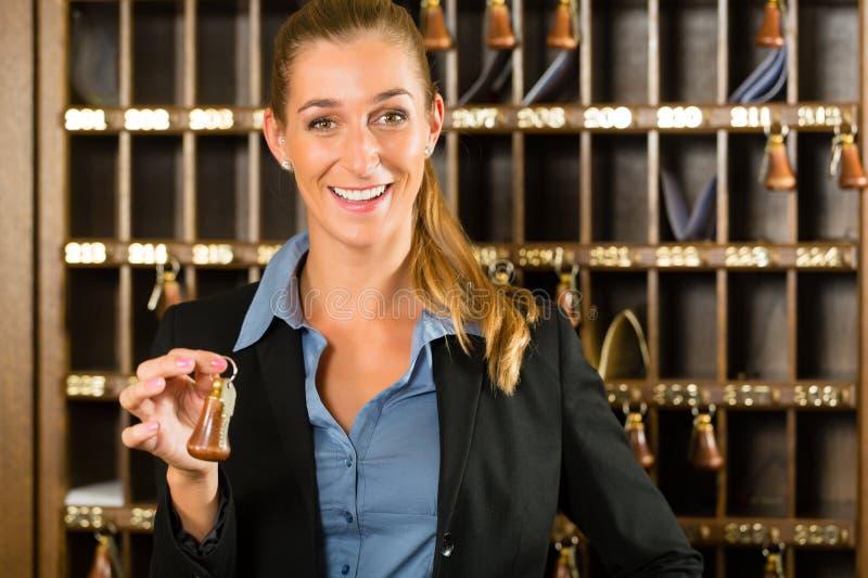 Recepción del hotel - mujer que lleva a cabo llave disponible fotografía de archivo libre de regalías