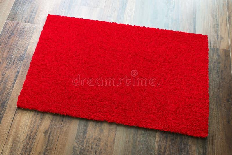 Recepción en blanco Mat On Wood Floor Background del rojo listo para su texto imágenes de archivo libres de regalías
