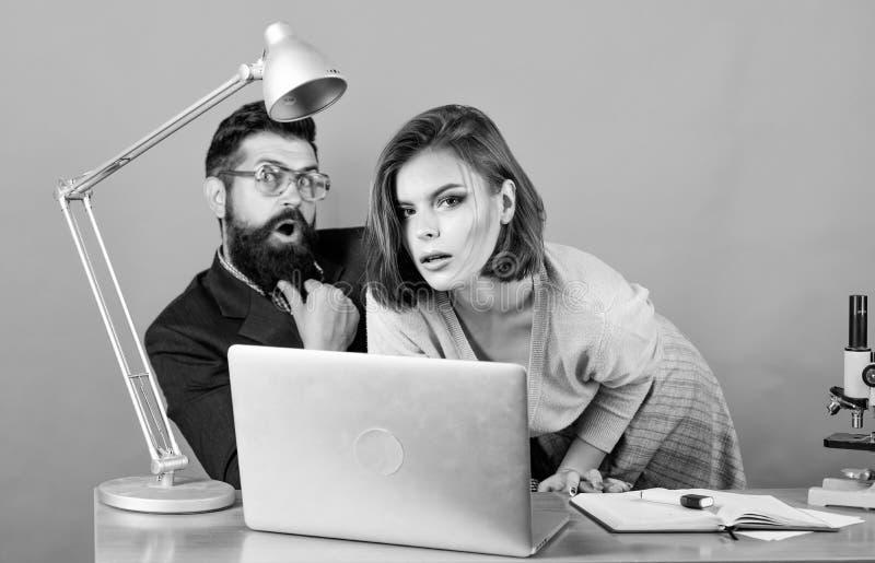 Recepci?n a nuestro equipo pares del negocio en el ordenador trabajo de la mujer y del hombre en oficina en el ordenador port?til fotos de archivo