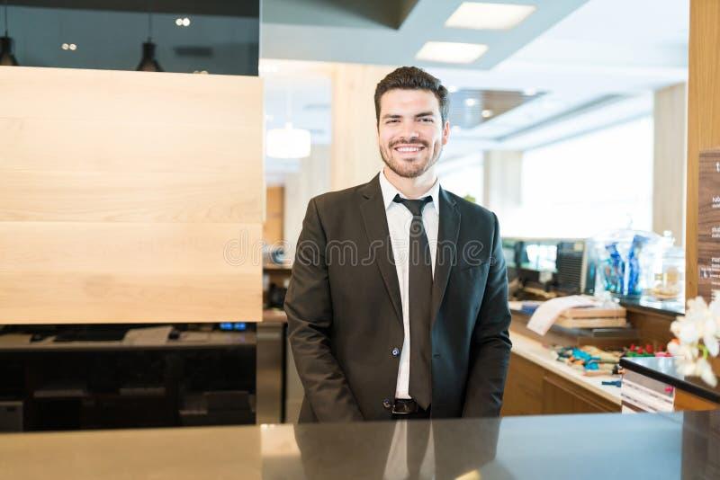 Recepcionista adulto meados de Standing At Lobby no hotel fotografia de stock royalty free
