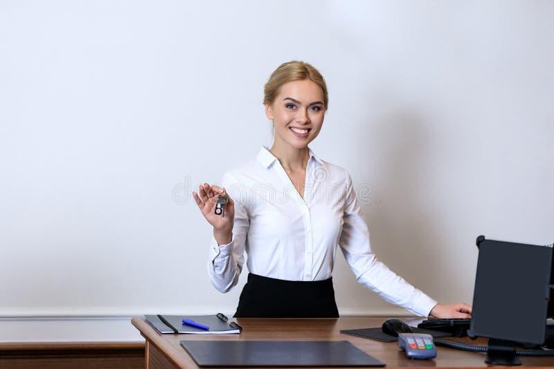 recepcionista atractivo sonriente que se sostiene dominante en el mostrador de recepción imágenes de archivo libres de regalías