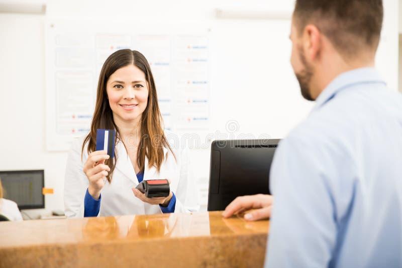 Recepcionista bonito que toma o pagamento com cartão de crédito fotografia de stock