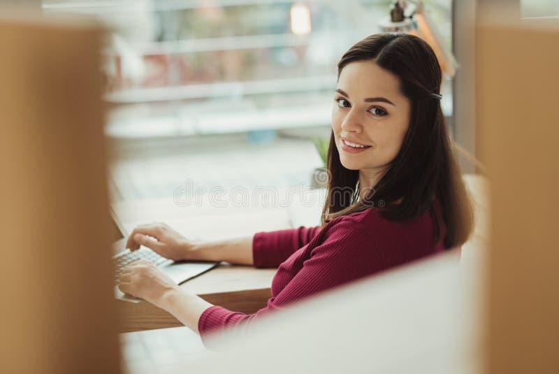 Recepcionista consideravelmente profissional que sorri ao ser no trabalho fotos de stock