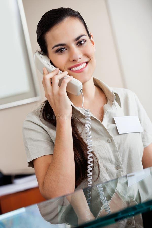 Recepcionista de sexo femenino Answering Call foto de archivo libre de regalías