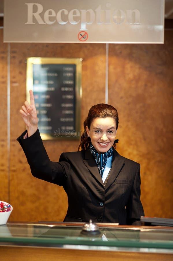Recepcionista de sexo femenino hermoso que indica hacia arriba foto de archivo libre de regalías