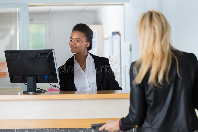 Recepcionista de sexo femenino que asiste al pasajero hermoso foto de archivo