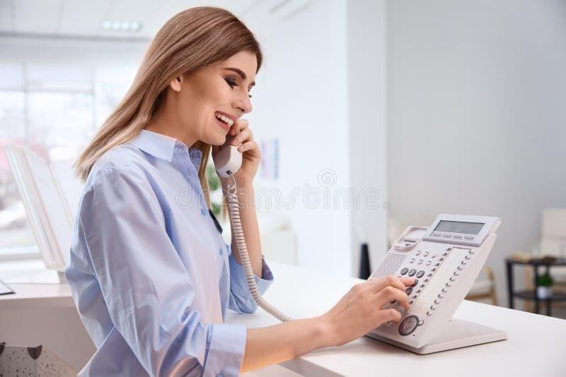 Recepcionista de sexo femenino que habla en el teléfono en el control del hotel fotografía de archivo libre de regalías