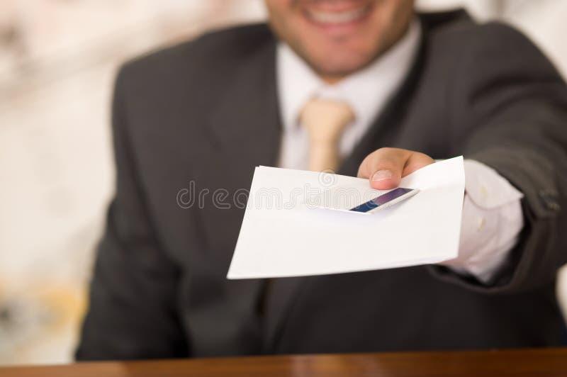 Recepcionista de sorriso feliz borrado no hotel que dá a chave ao convidado e aos papéis ao sinal foto de stock royalty free