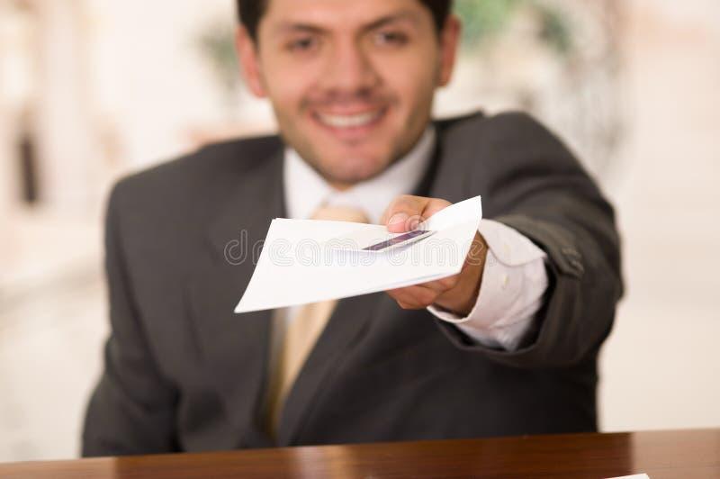 Recepcionista de sorriso feliz no hotel que dá a chave ao convidado e aos papéis ao sinal fotos de stock