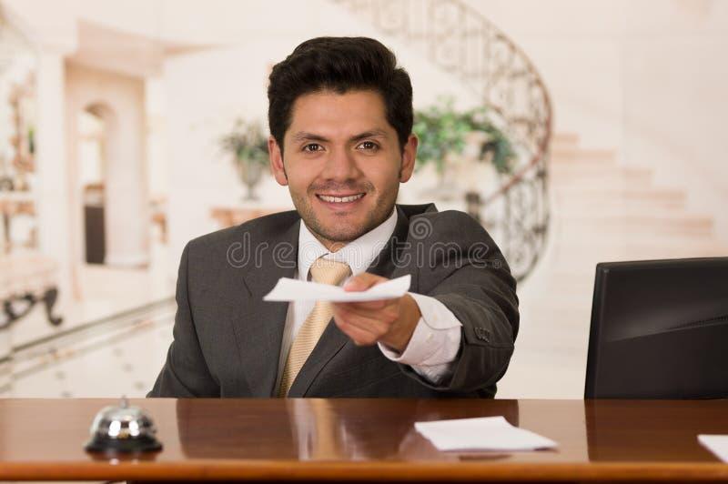 Recepcionista de sorriso feliz no hotel que dá a chave ao convidado e aos papéis ao sinal, fundo do hotel imagem de stock royalty free