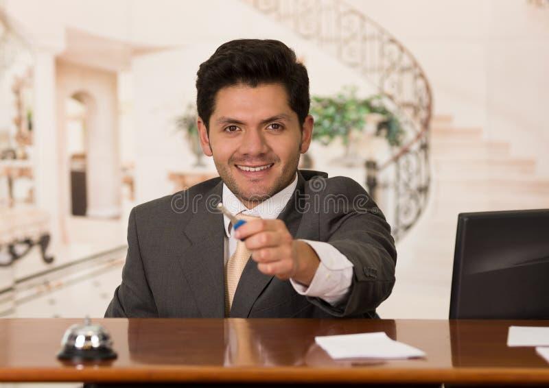 Recepcionista de sorriso feliz no hotel que dá a chave ao convidado, fundo do hotel fotos de stock