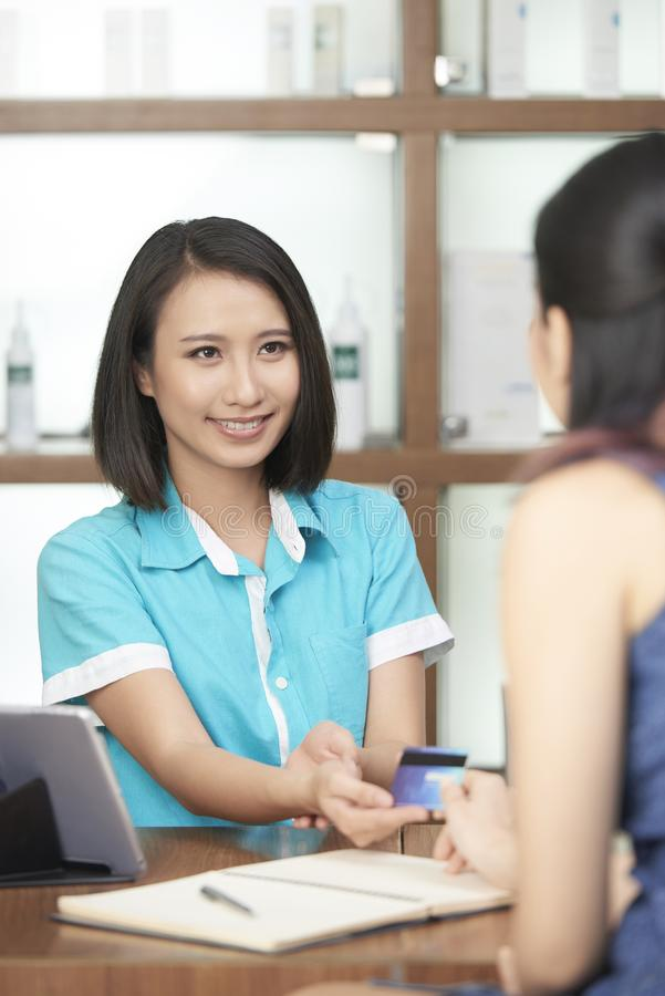 Recepcionista de sorriso que toma o pagamento do cliente fotografia de stock royalty free