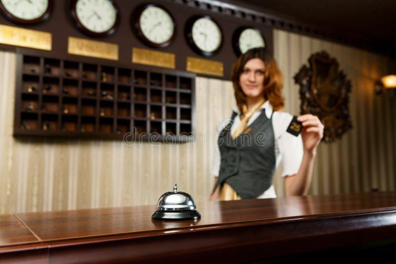 Recepcionista do hotel e mesa contrária com sino foto de stock royalty free